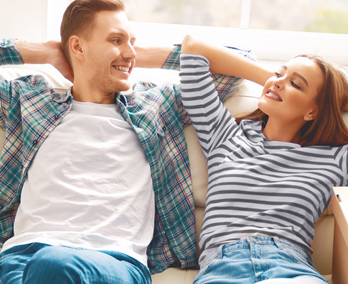 Couple relaxing on a couch in their new home
