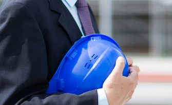 A businessman holding a blue hardhat